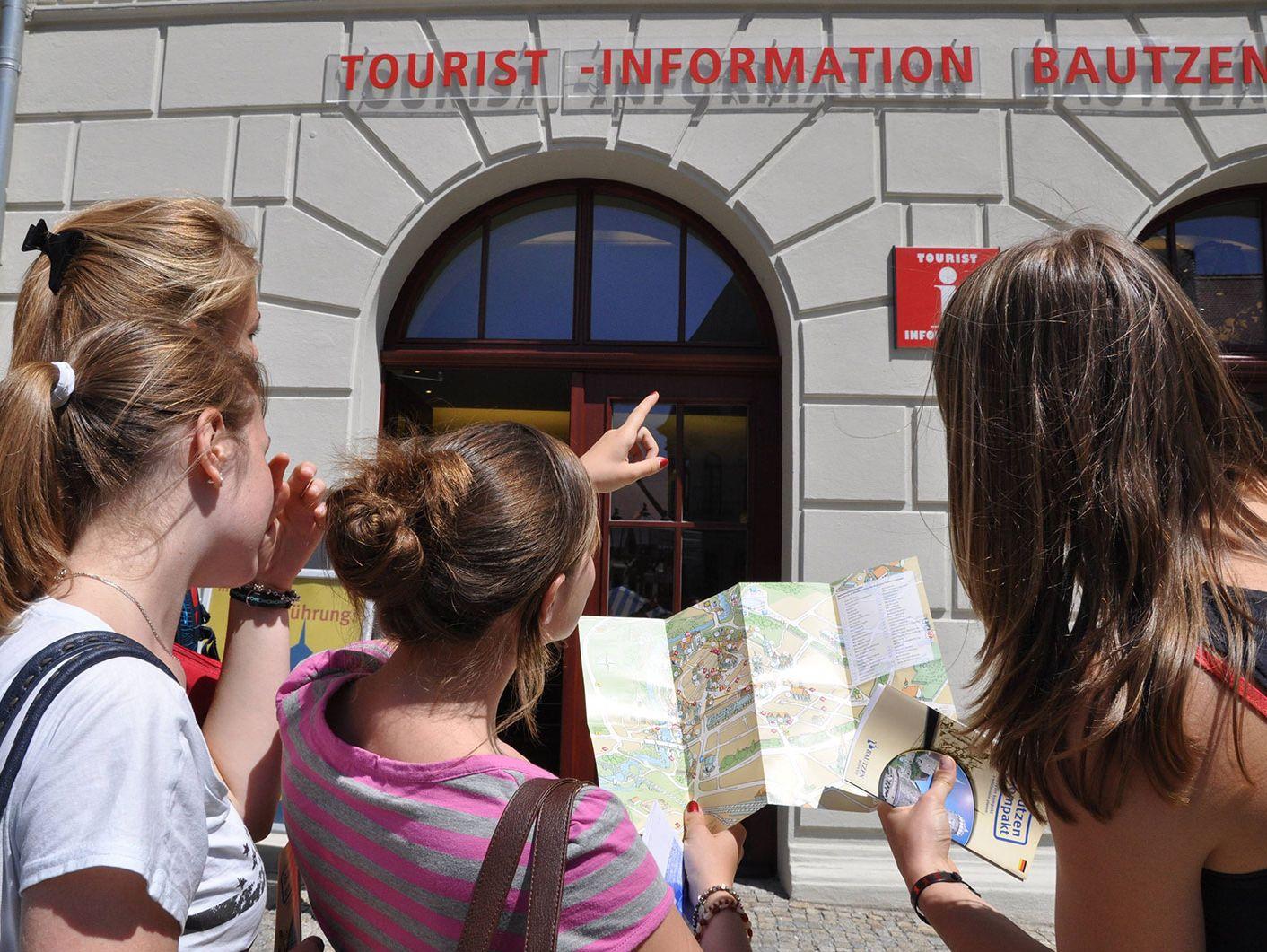 Jugendliche stehen mit einem Stadtplan vor der Bautzener Tourist-Information