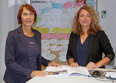 Zwei Frauen stehen am Schreibtisch in blättern in einer Broschüre