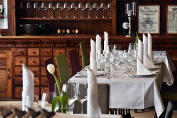 Tische mit weißer Tischdecke und rot oder grünen Stühlen, auf den Tischen stehen Gläser und Teller mit gerollten Servierten