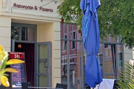 offene Eingangstür zum Ristorante im Vorderung ein geschlossener blauer Sonnenschirm