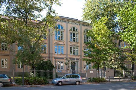 Melanchton Gymnasium- helles Gebäude mit lateinischem Schriftzug, im Vordergrund- Bäume