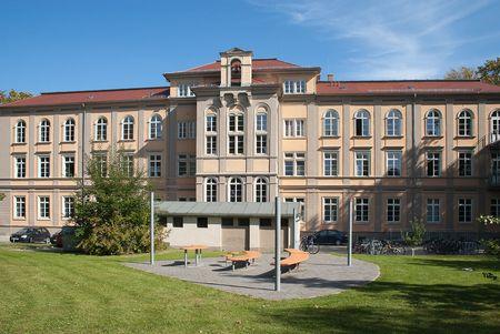 Abendgymnasium- helles Gebäude mit Sitzbänken im Vordergrund