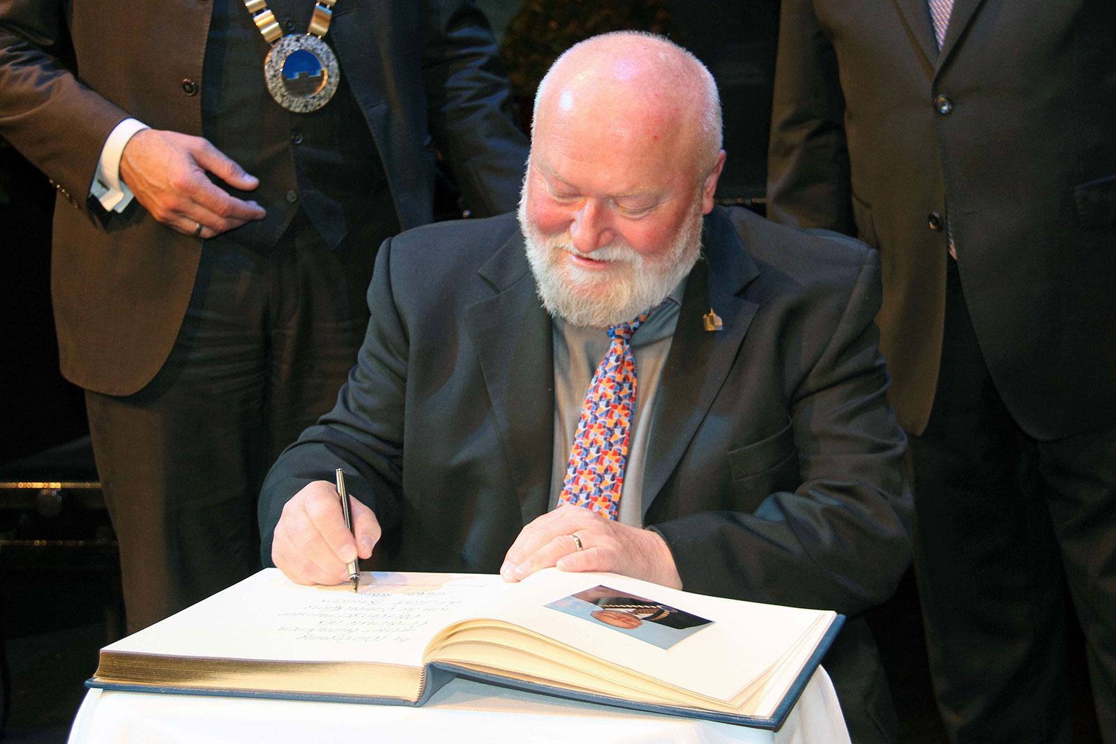 Christian Schramm trägt sich in das Buch der Ehrenbürger der Stadt Bautzen ein.