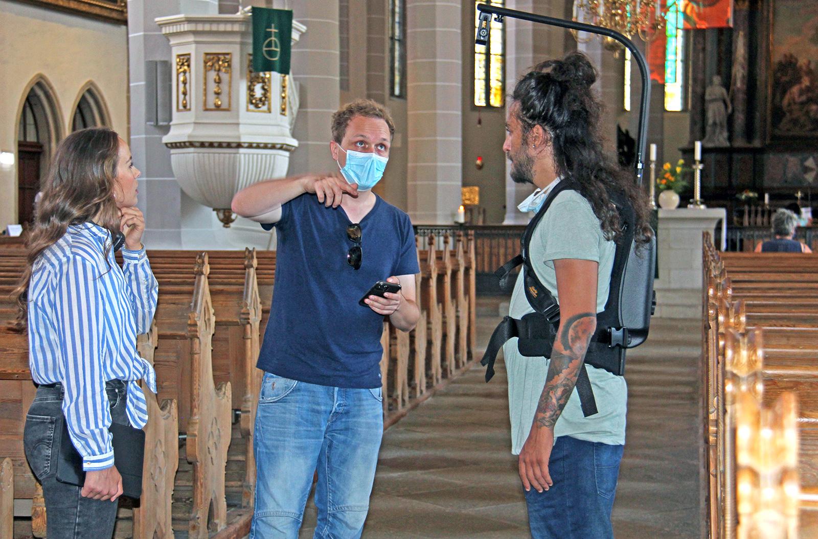 Junge Frau in blau-weiß gestreifter Bluse, ein junger Mann in blauem Hemd und blauer Jeans sowie ein zweiter junger Mann mit Kamera stehen im Dom St. Petri. Sie besprechen den Filmdreh. und bespre