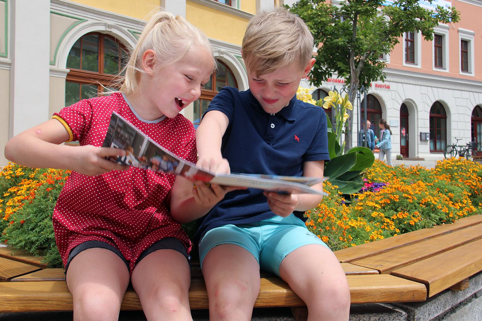 Mädchen und Junge sitzen auf Bank vor dem Rathaus und schauen Familienbroschüre an