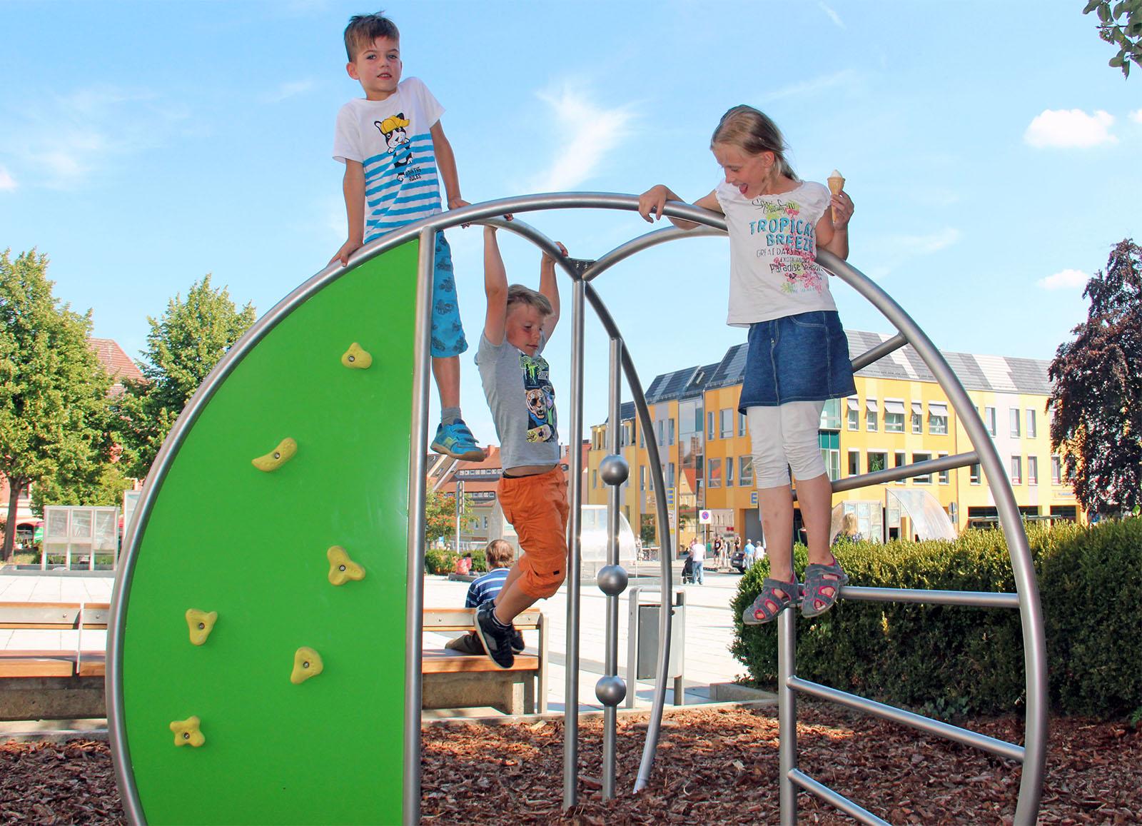 Drei Kinder klettern auf neuem Spielgerätauf dem Kornmarkt im Hintergrund das Kornmarkthaus