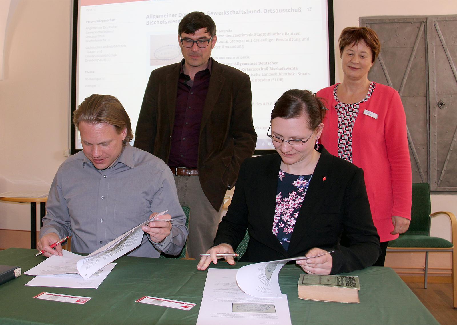 Dana Dubil, Geschäftsführerin der DGB-Regionsgeschäftsstelle Ostsachsen, und Jan Otto, Erster Bevollmächtigter der IG Metall Ostsachsen, unterzeichnen die Übergabeurkunde an die Stadtbibliothek Bautzen