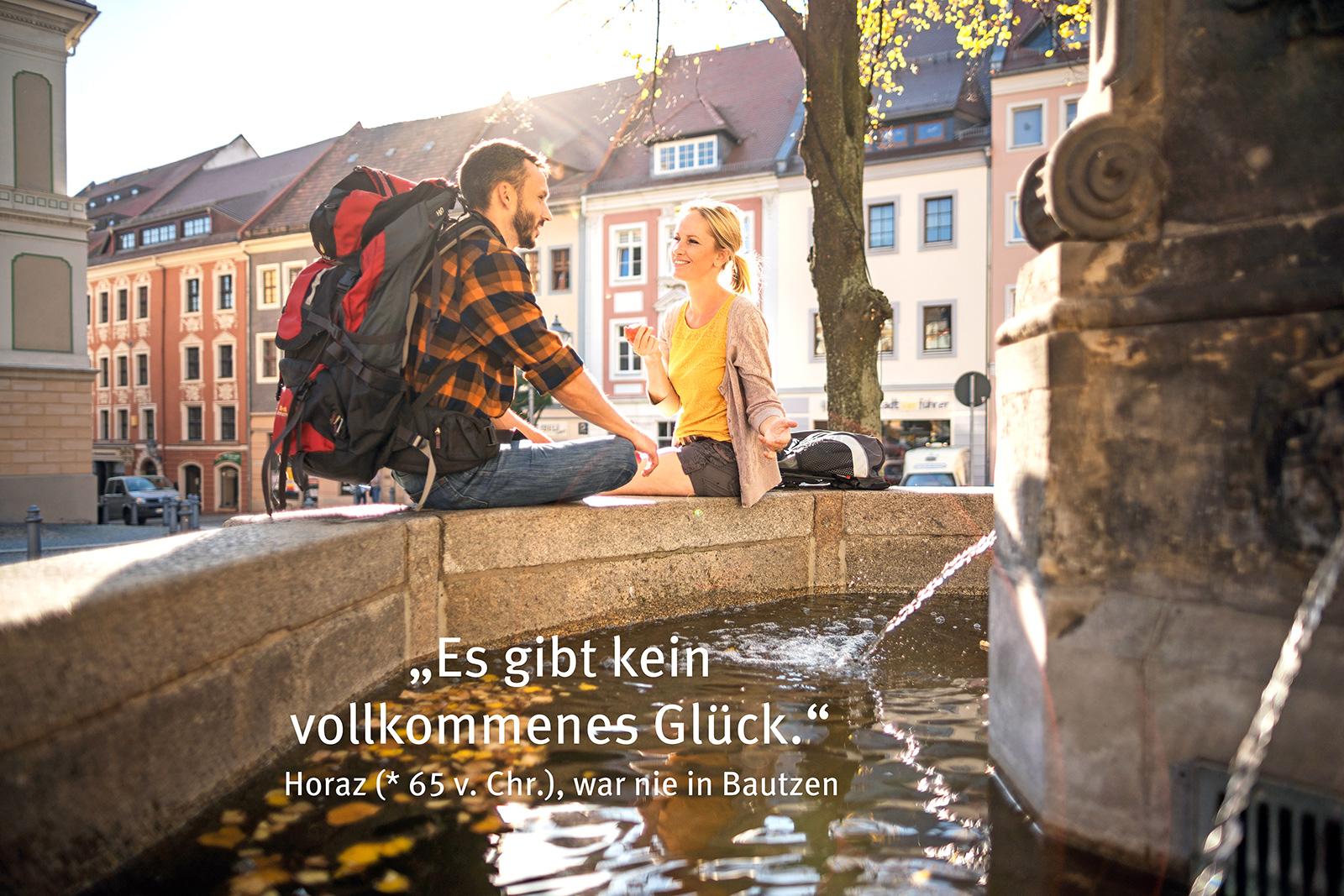 Junger Mann mit Rucksack und junge Frau sitzen auf Brunnenrand, im Hintergrund Häuserzeile