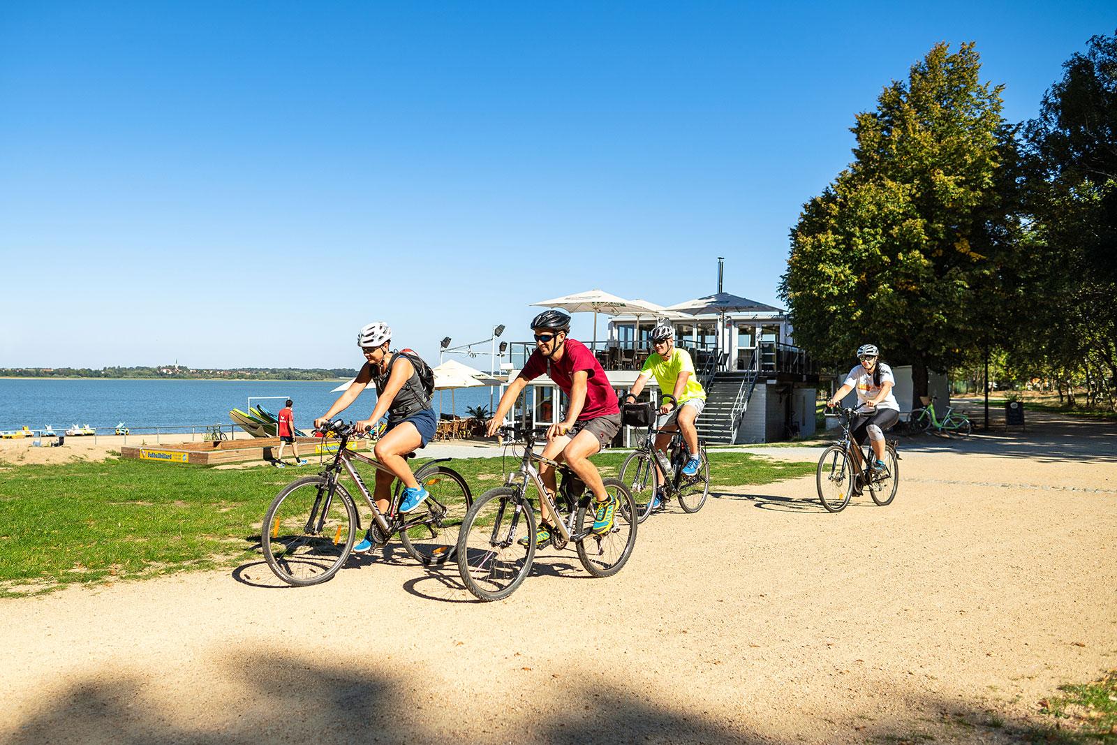 Vordergrund eine Gruppe Radfahrer, Hintergrund Stausee Bautzen