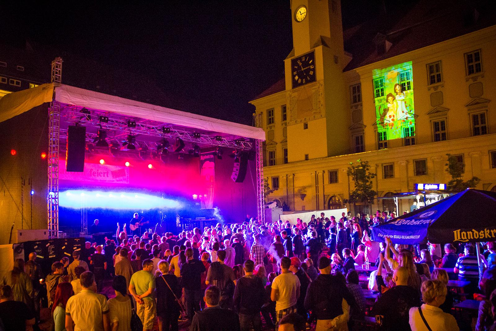 Bautzener Frühlingsimpression - Musikkonzert auf dem gut besuchten nächtlichen Hauptmarkt, im Hintergrund das Rathaus, angestrahlt mit dem Plakatmotiv des Bautzener Frühlings