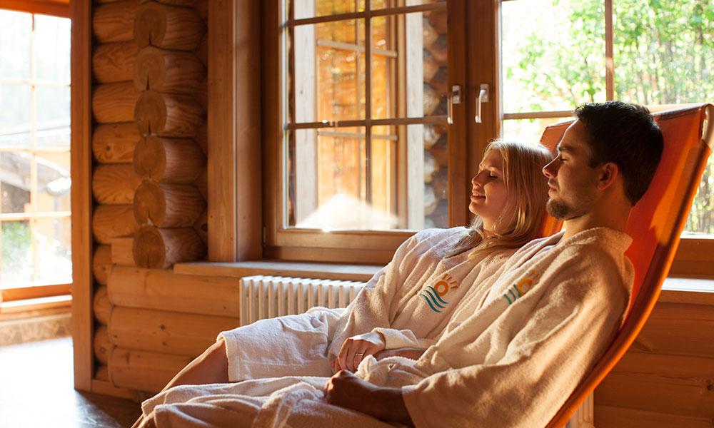 Zwei Personen sitzen im Bademantel auf Liegen, Entspannung